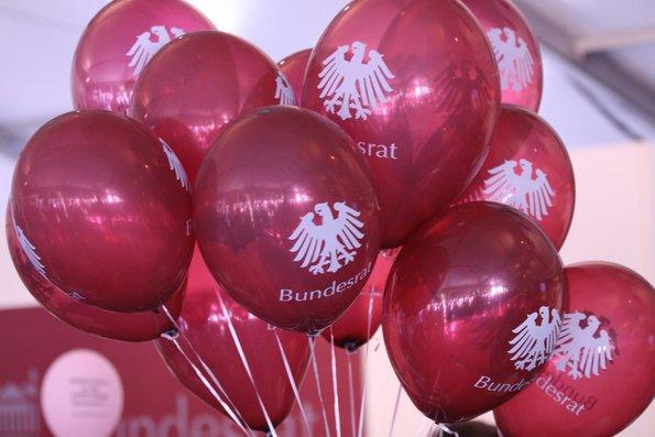 Rote Ballons mit dem Schriftzug Bundesrat und dem Bundesadler, welche in einer dicken Traube zusammenhängen.