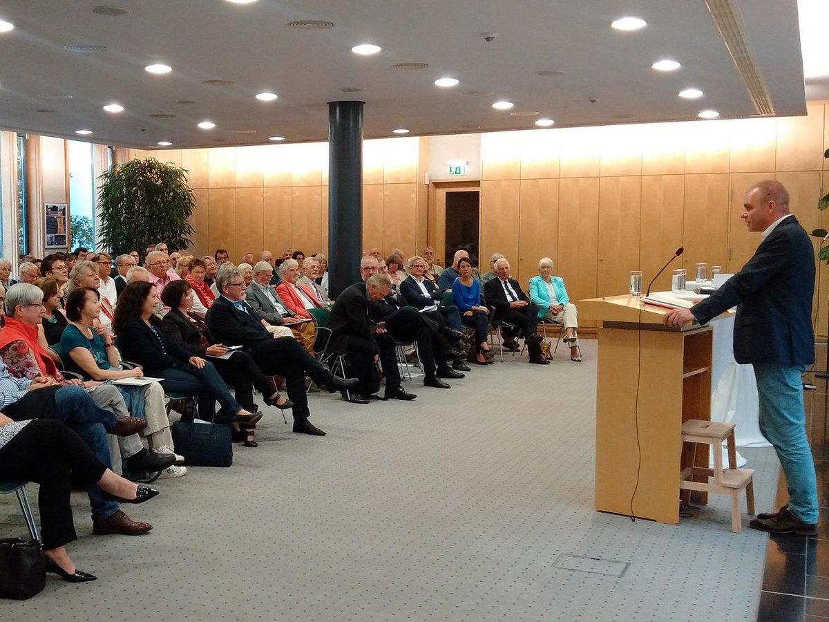 Der Staatssekretär für Medien und Bevollmächtigter des Freistaats Thüringen beim Bund Malte Joas Krückels vor einem Rednerpult und seine Zuhörer