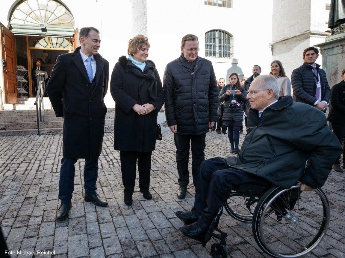 Der Ministerpräsident Bodo Ramelow und der Bürgermeister von Weimar in der Mitte von Passanten. Im Vorfergrund fährt ein Rollstuhlfahrer, welcher freundlich lächelt.