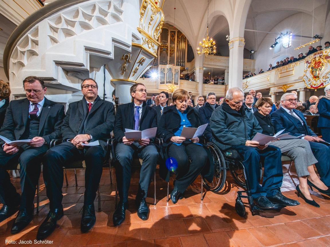 Der Ministerpräsident Bodo Ramelow mit Frau Angela Merkel sitzen mit vielen weiteren Personen in der ersten Reihe in der Herderkirche in Weimar.