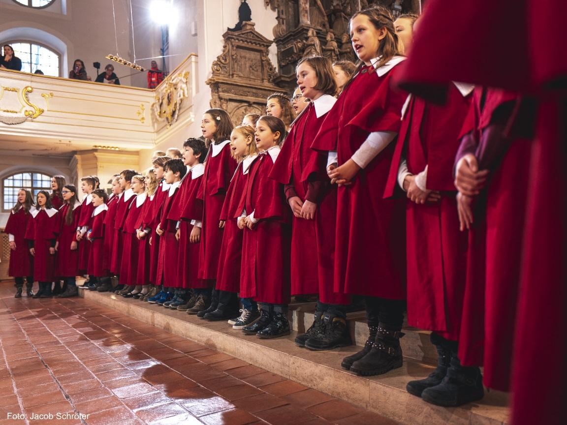 Ein Kinderchor in der Herderkirche singt. Alle Kinder tragen lange rote Mäntel und einen weißen großen Kragen.