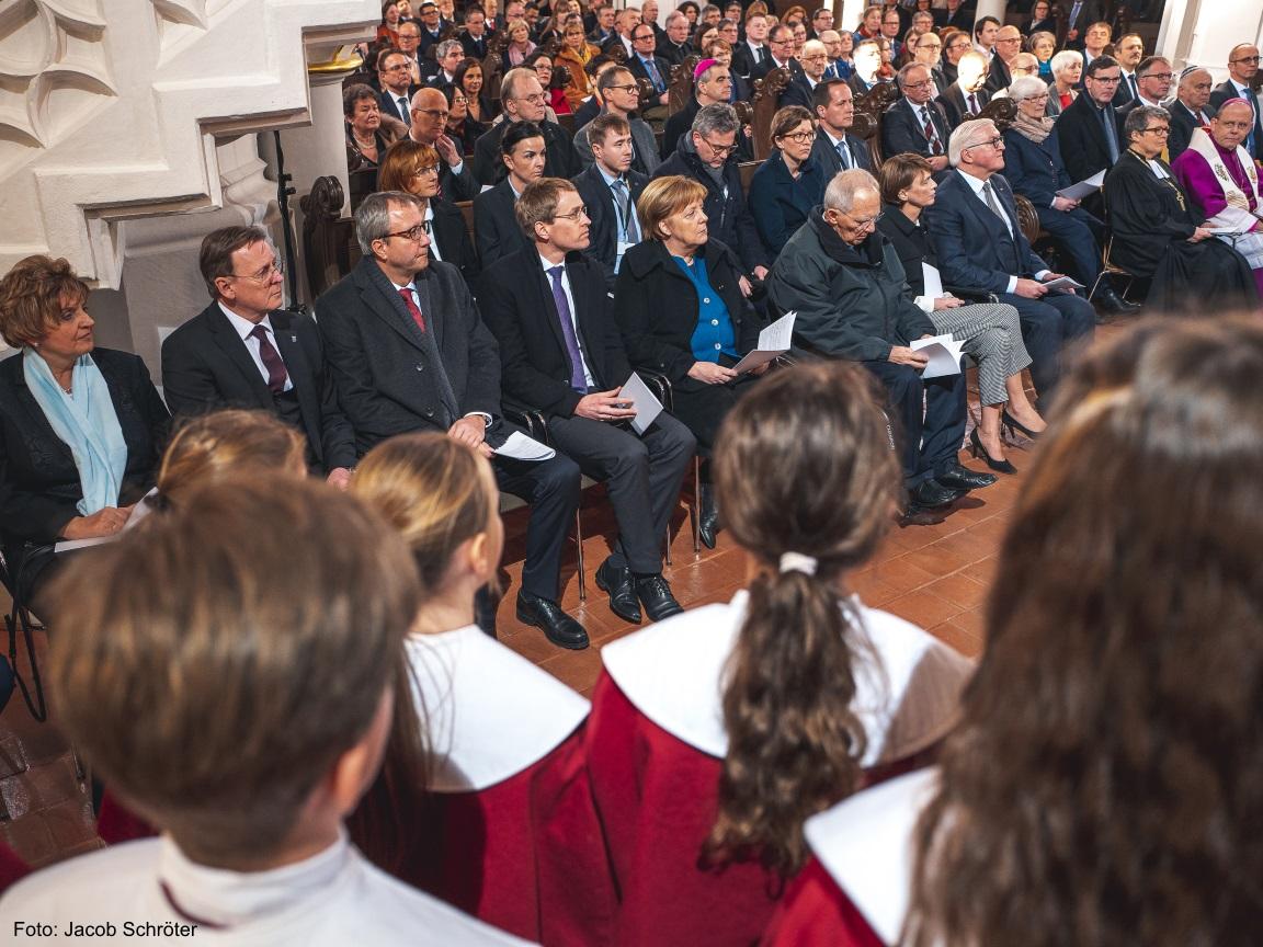 Der Ministerpräsident Bodo Ramelow und Frau Angela Merkel lauschen interessiert dem Kinderchor in der Herderkirche.