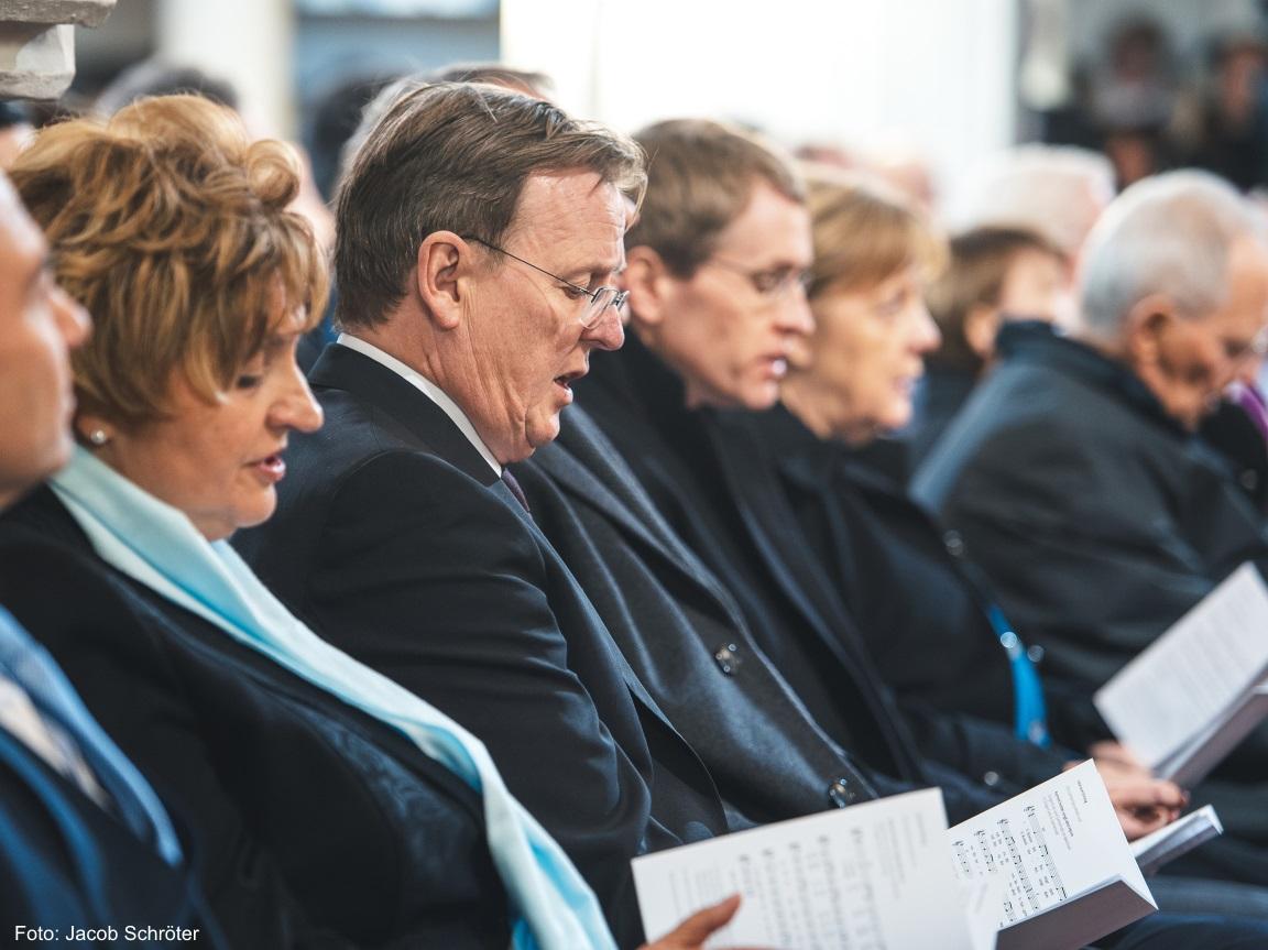 Der Ministerpräsident Bodo Ramelow singt einträchtig aus dem Gesangsbuch ein Lied mit den anderen Zuschauern.