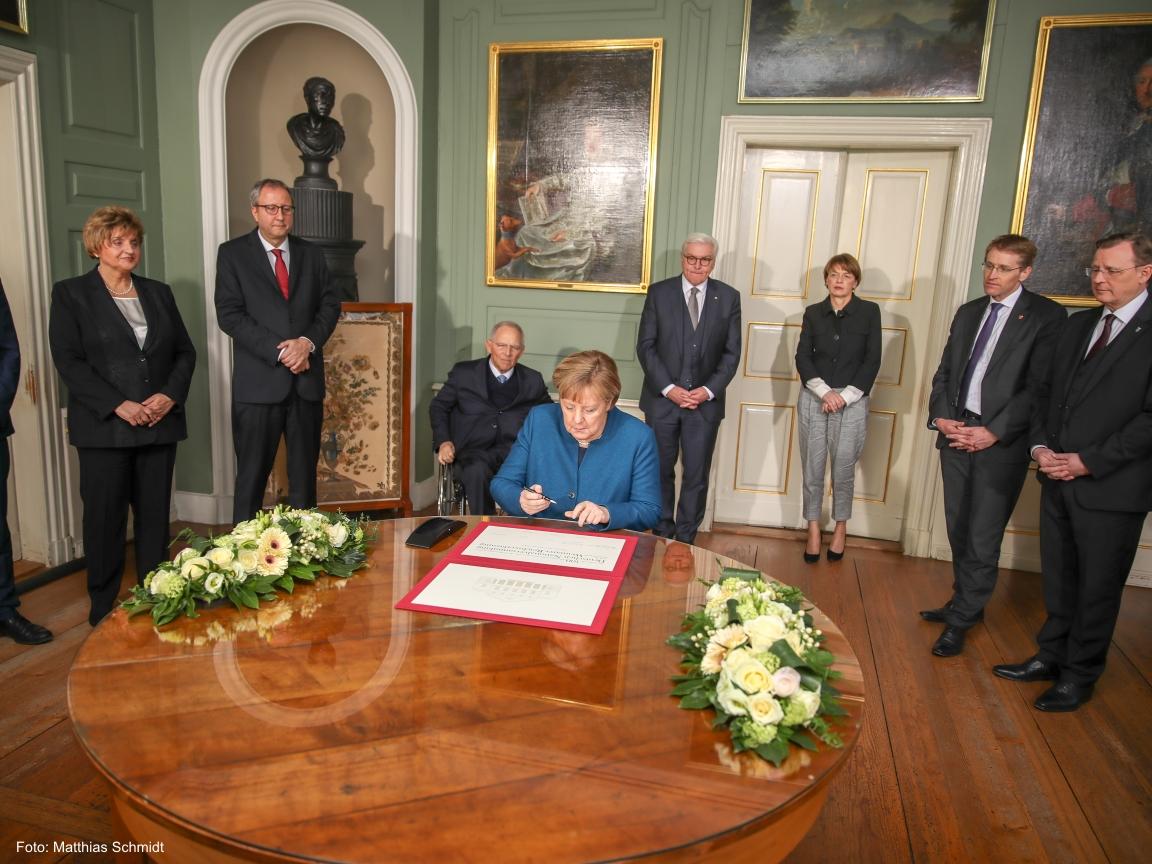 Die Bundeskanzlerin Angela Merkel signiert ein Schriftstück im Wittumspalais in Weimar