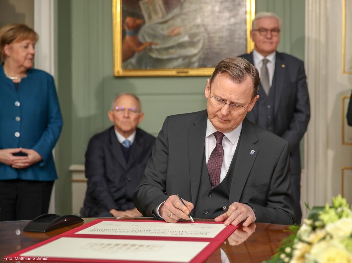 Der Ministerpräsident Bodo Ramelow signiert ein Schriftstück im Wittumspalais in Weimar.