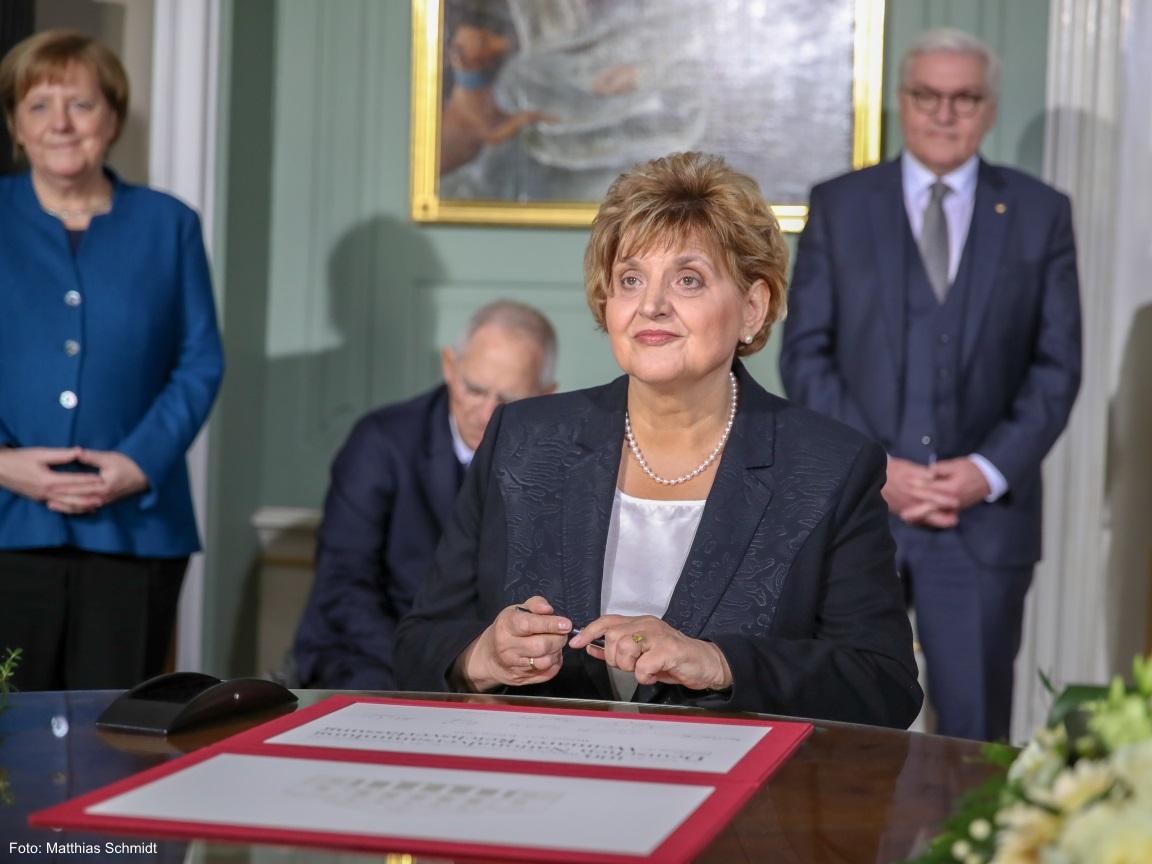 Eine gut gekleidete Frau lächelt nach dem sie ein Schriftstüc unterschrieben hat.