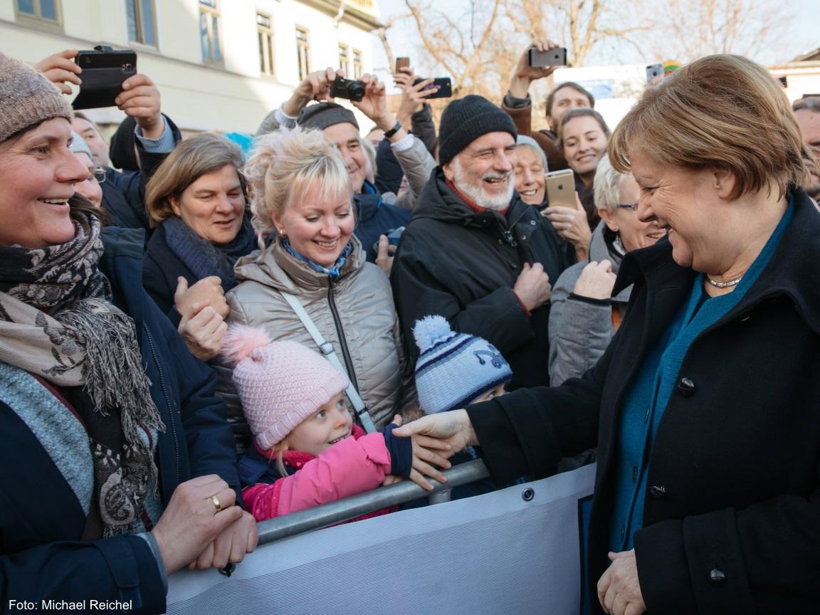 Die lächelnde Bundeskanzlerin Angela Merkel gibt einem kleinen zurück lächelnden Mädchen die Hand.