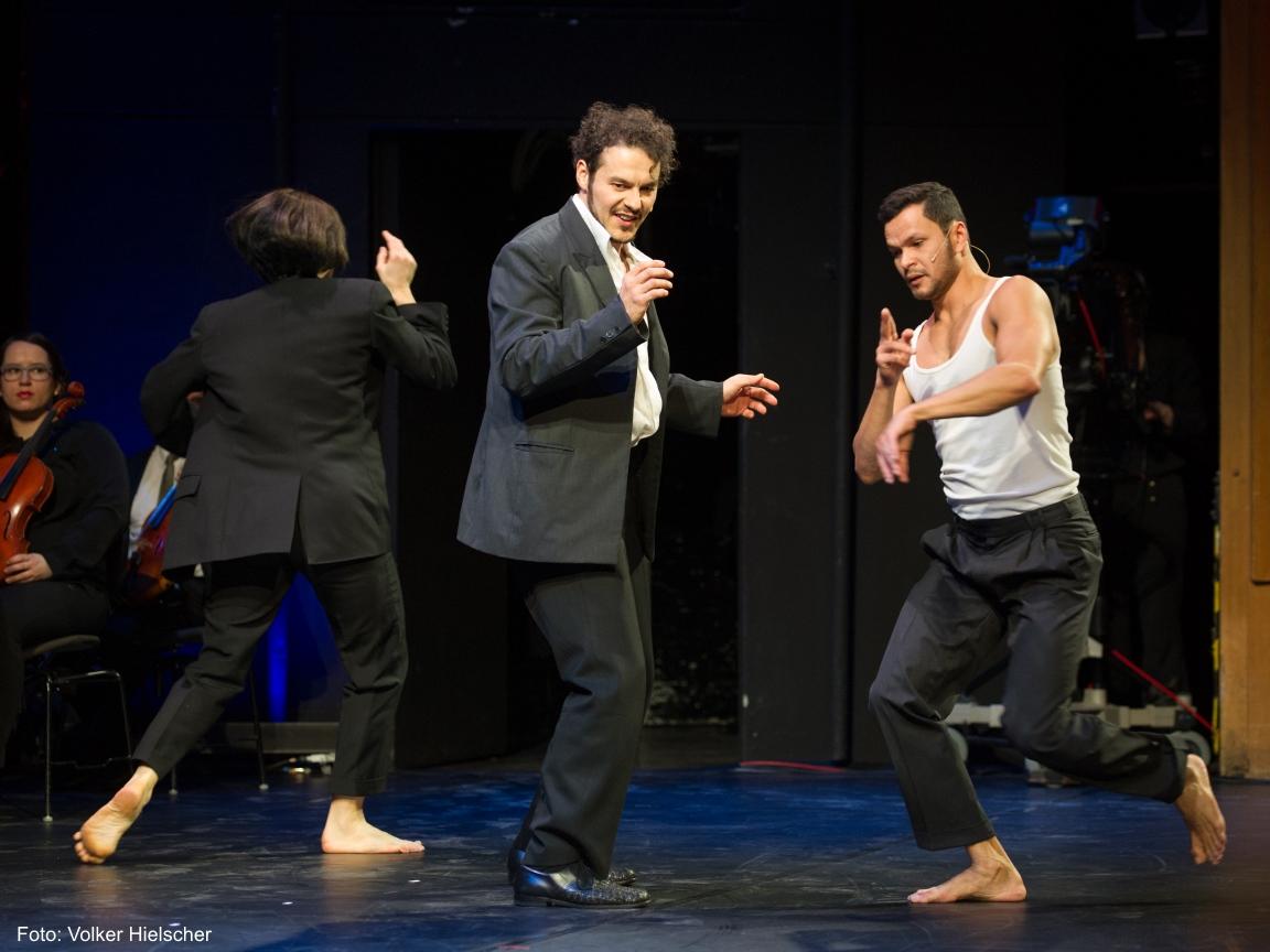 Drei Schauspieler des DNT Theaters spielen auf der Bühne.