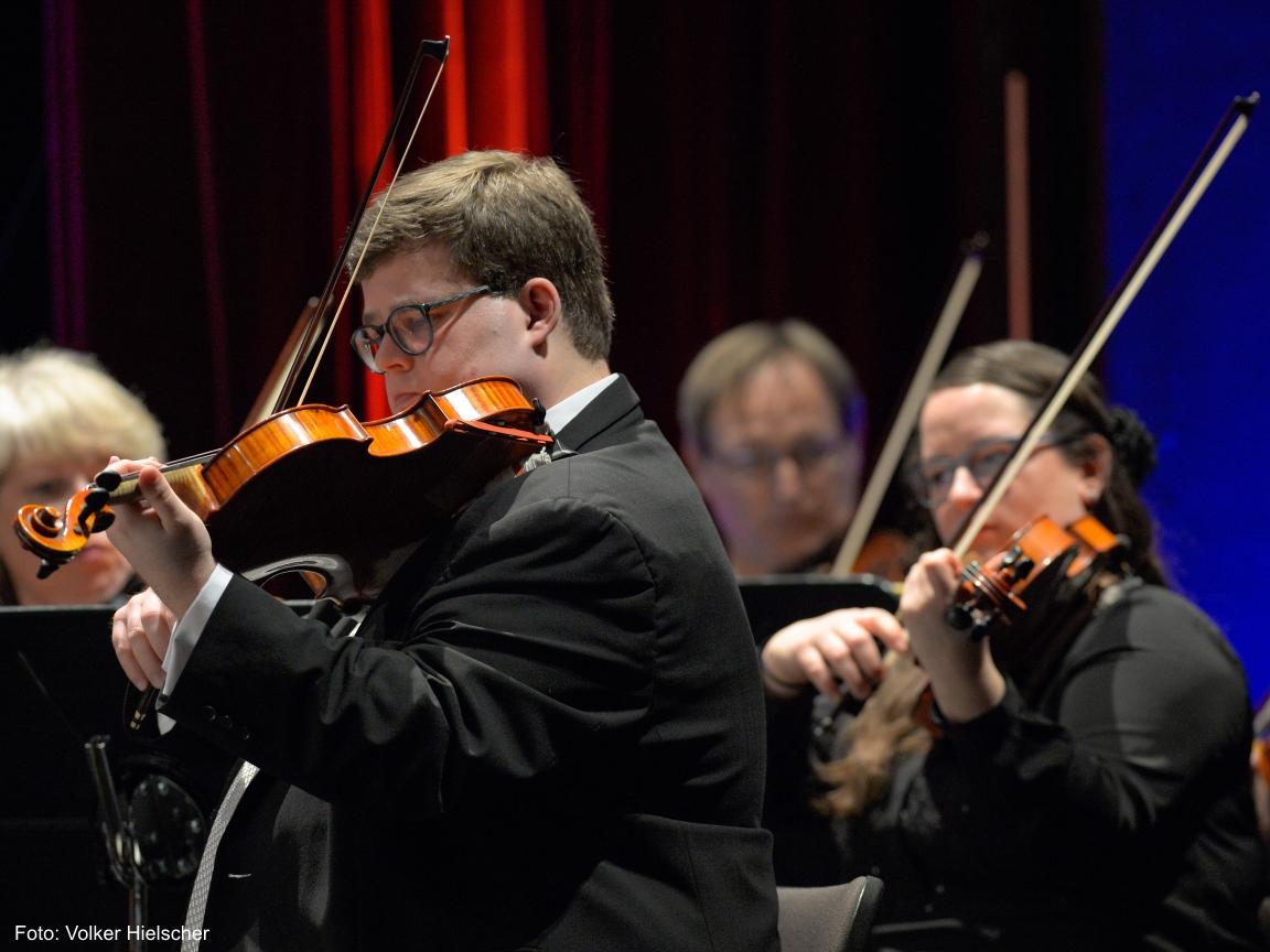 Ein Musiker spielt hingebungsvoll eine Melodie mit seiner Violine.