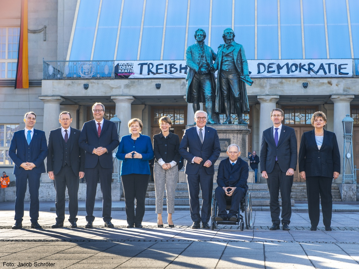 Der Bürgermeister von Weimar, der Ministerpräsident Bodo Ramelow, die Bundeskanzlerin Angela Merkel, der SPD Politiker Steinmeier und weitere Personen stehen vor dem Deutschen Nationaltheater in Weimar.