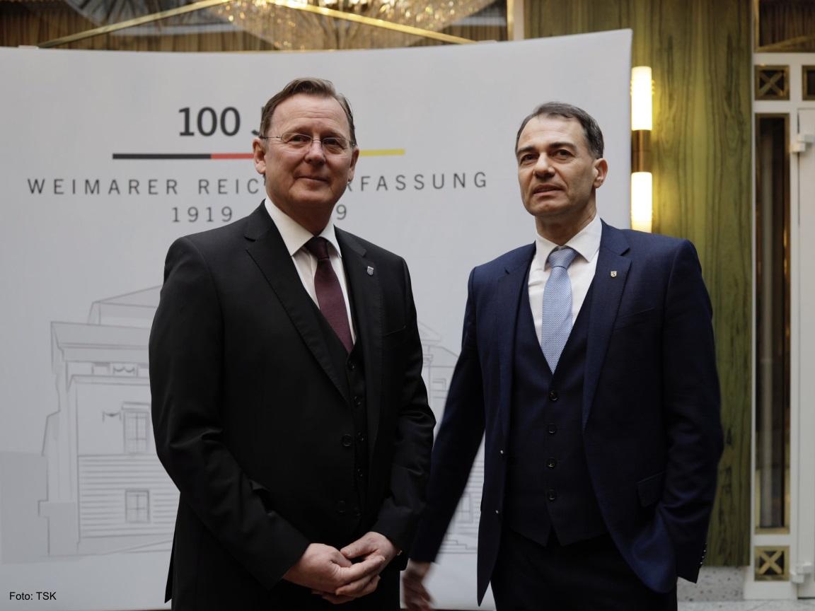 Der Ministerpräsident Bodo Ramelow steht mit dem Bürgermeister von Weimar vor einem Banner mit dem Schriftzug 100 Jahre Weimarer Reichverfassung und lächelt in die Kamera.